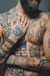 Bare chested young man, covered in tattoos, mid section - CUF47206