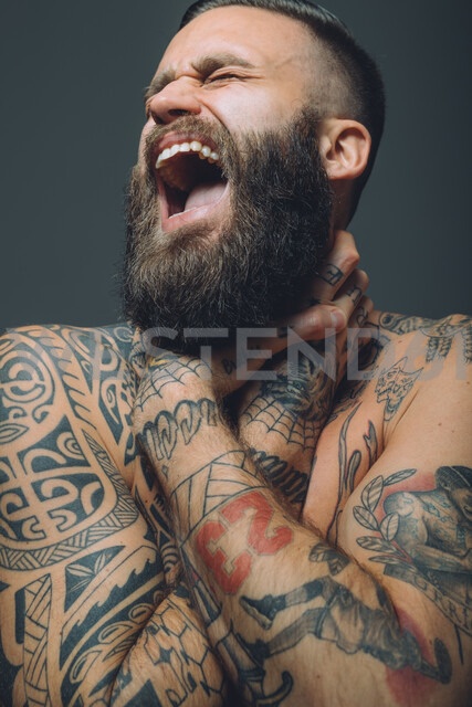 Portrait of  young man with beard, covered in tattoos, hands around throat, screaming - CUF47209