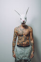 Portrait of young man with wearing rabbit mask, bare chest covered in tattoos - CUF47212