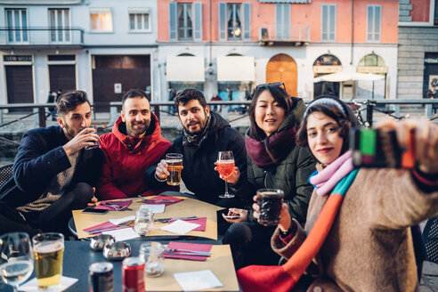 Friends enjoying drink at outdoor cafe, Milan, Italy - CUF47242