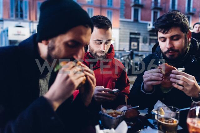 Friends enjoying burger at outdoor cafe, Milan, Italy - CUF47245