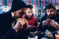 Friends enjoying burger at outdoor cafe, Milan, Italy - CUF47245