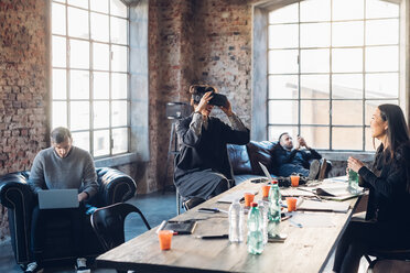 Designers testing virtual reality headset in communal space in studio - CUF47248