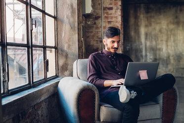 Man in armchair using laptop - CUF47254