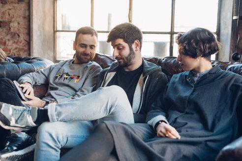 Designers taking break on sofa in studio - CUF47260