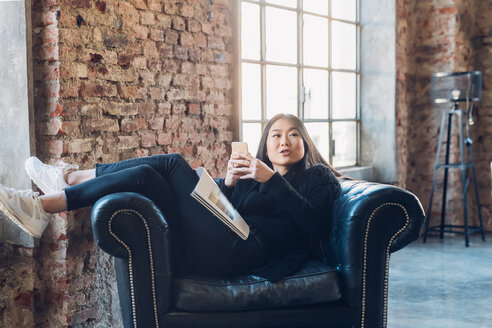 Woman on armchair using smartphone - CUF47272