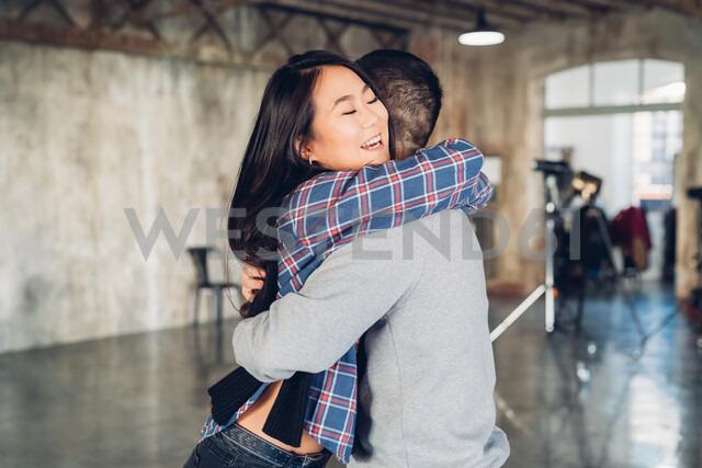 Couple hugging in open plan studio - CUF47281
