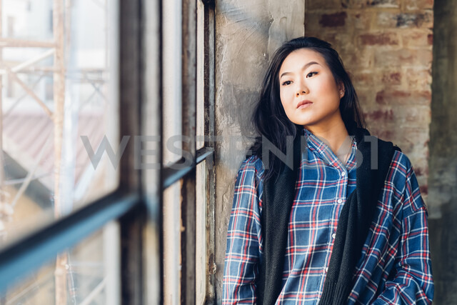 Woman leaning against brick wall by window - CUF47293