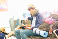 Young couple in departure lounge at airport, woman resting head on man's legs, man using digital tablet - CUF47305