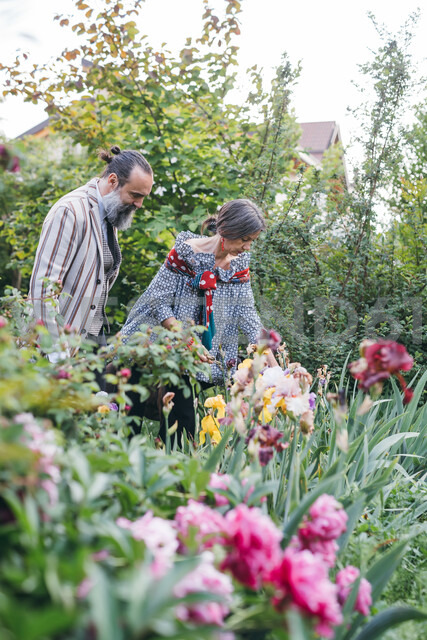 Couple picking flowers from garden - CUF47308
