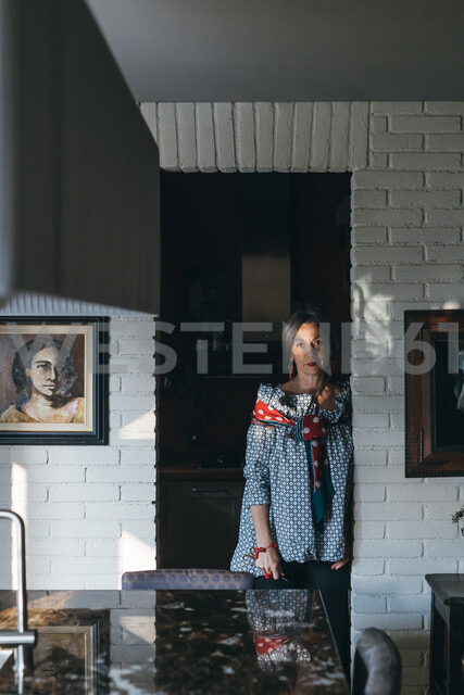 Woman leaning against doorway of kitchen - CUF47311