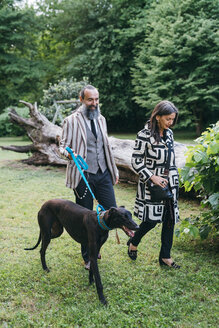 Couple walking dog in woods - CUF47314