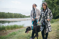 Couple walking dog by lake - CUF47317