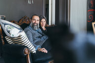 Couple on sofa looking at camera - CUF47320