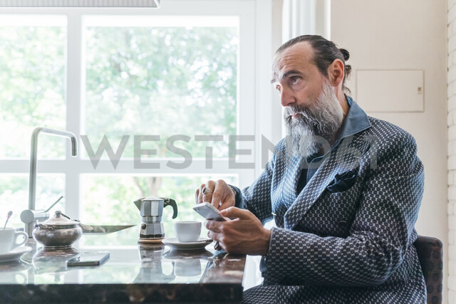 Man texting over coffee in kitchen - CUF47332
