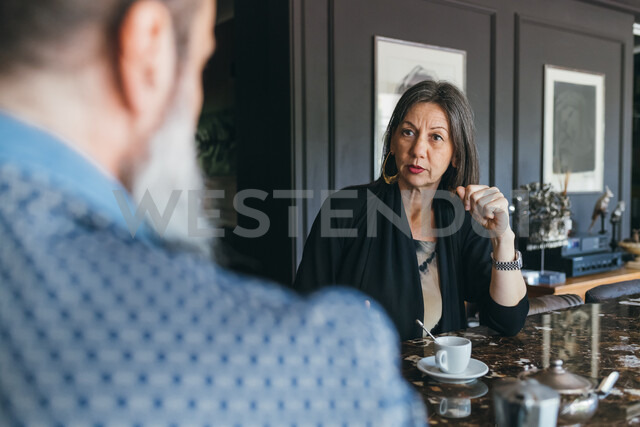 Couple in discussion over coffee in kitchen - CUF47344
