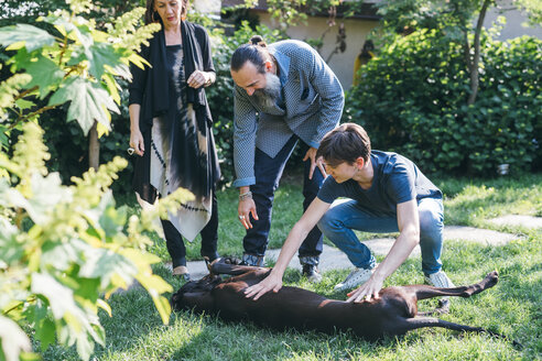 Couple with son and pet dog in garden - CUF47350
