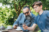 Man and son using cellphone over coffee in garden - CUF47353