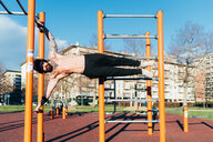 Man using horizontal ladder in outdoor gym - CUF47404