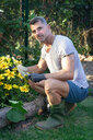 Man with trowel by flower bed - CUF47413