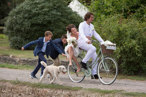 Young wedding guests running after newlyweds on bicycles - CUF47461