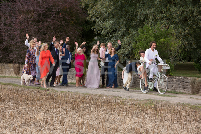 Wedding guests waving off newlyweds on bicycles - CUF47464