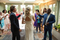 Wedding guests toasting to newlyweds at reception - CUF47476