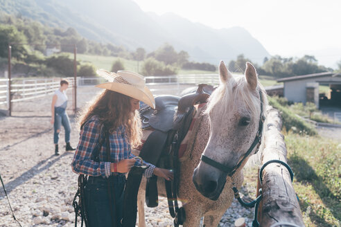 Young cowgirl checking saddle in rural equestrian arena - CUF47494