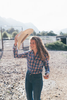 Cowgirl putting on stetson in rural equestrian arena - CUF47497