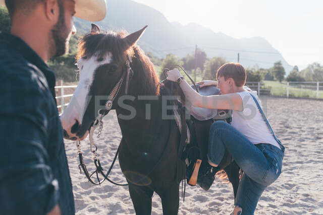 Young woman mounting horse in rural equestrian arena - CUF47500 - Eugenio Marongiu/Westend61