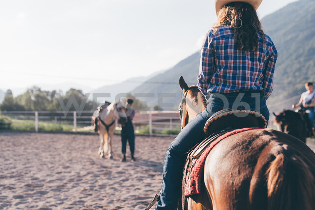 Cowgirl riding horse in rural equestrian arena, Primaluna, Trentino-Alto Adige, Italy - CUF47503