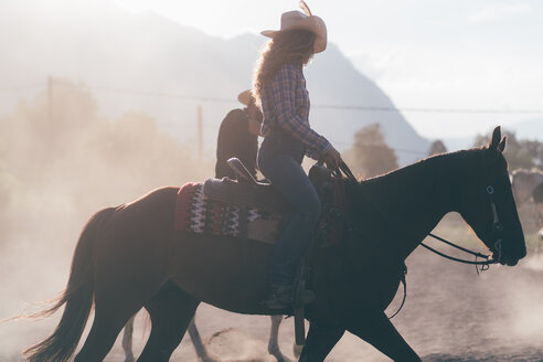 Cowgirl horse riding in dusty equestrian arena, sideview Primaluna, Trentino-Alto Adige, Italy - CUF47509