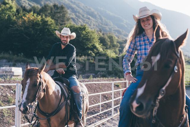 Cowgirl and boy on horseback in equestrian arena, portrait, Primaluna, Trentino-Alto Adige, Italy - CUF47512