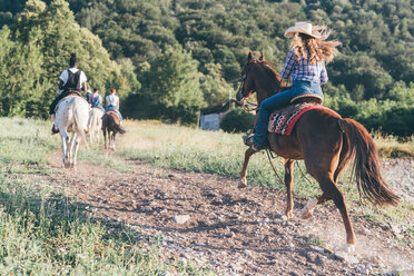 Young adults riding horses in rural landscape, rear view, Primaluna, Trentino-Alto Adige, Italy - CUF47515