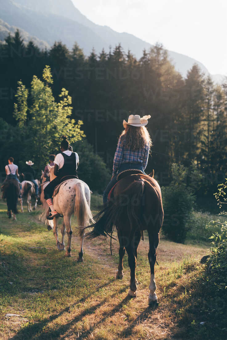 Young adult friends horse riding by forest, rear view, Primaluna, Trentino-Alto Adige, Italy - CUF47518 - Eugenio Marongiu/Westend61