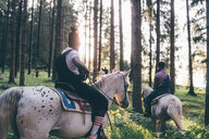 Two young men horse riding in sunlit forest, Primaluna, Trentino-Alto Adige, Italy - CUF47521