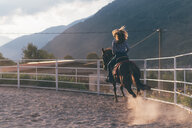 Long haired young woman cantering on horse in rural equestrian arena, rear view, Primaluna, Trentino-Alto Adige, Italy - CUF47524