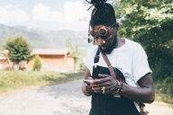 Cool young man on rural dirt track looking at smartphone, Primaluna, Trentino-Alto Adige, Italy - CUF47527