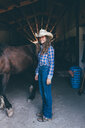 Young cowgirl at stable entrance, portrait - CUF47536