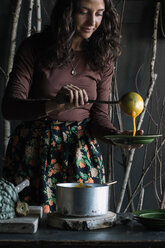Young woman ladling fresh soup from saucepan at rustic kitchen counter - CUF47548