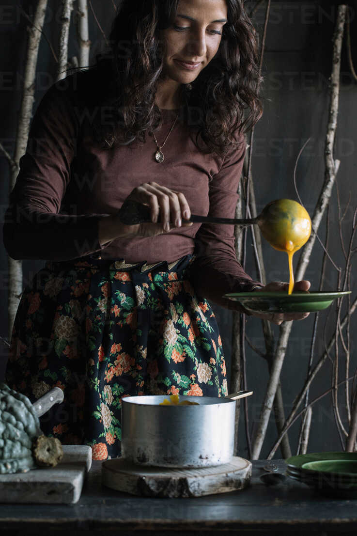 Young woman ladling fresh soup from saucepan at rustic kitchen counter - CUF47548 - Alberto Bogo/Westend61