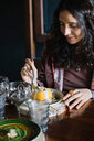 Young woman eating dessert at restaurant table - CUF47554