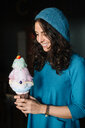 Stylish young woman in blue knit hat holding large ice cream cone - CUF47578