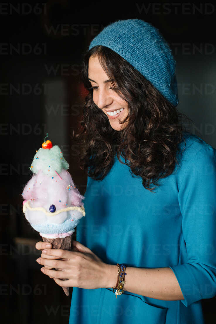 Stylish young woman in blue knit hat holding large ice cream cone - CUF47578 - Alberto Bogo/Westend61