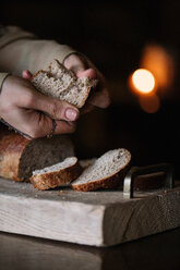 Young woman breaking brown bread on rustic chopping board, close up of hands - CUF47584