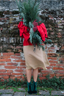 Young woman in front of old brick wall holding christmas tree - CUF47587
