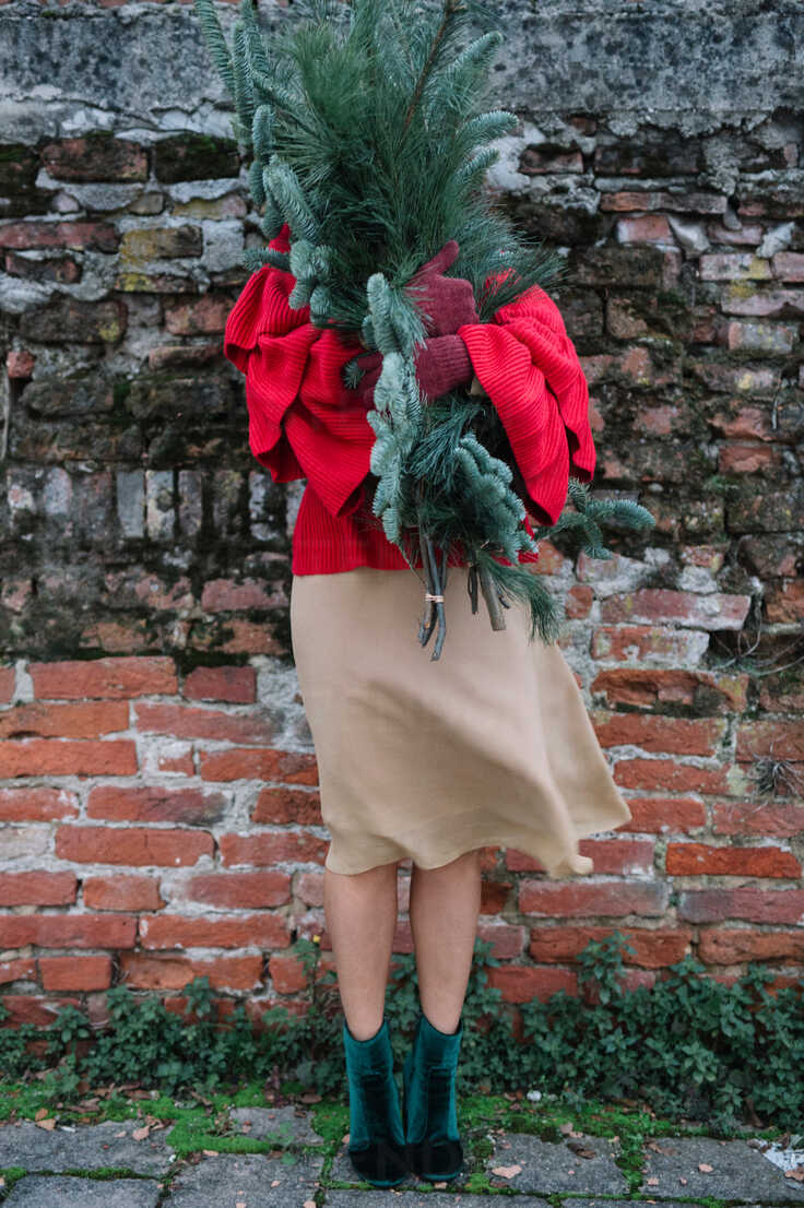 Young woman in front of old brick wall holding christmas tree - CUF47587 - Alberto Bogo/Westend61