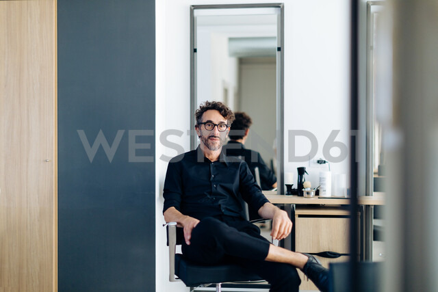 Mature male hairstylist sitting in chair in hair salon, portrait - CUF47593