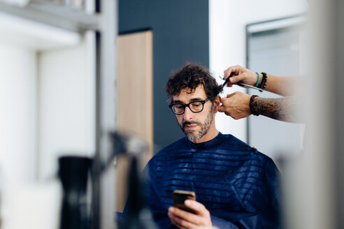 Male hairstylist cutting male customer's hair in hair salon - CUF47596