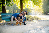 Couple with pet dog sitting on park bench - CUF47608